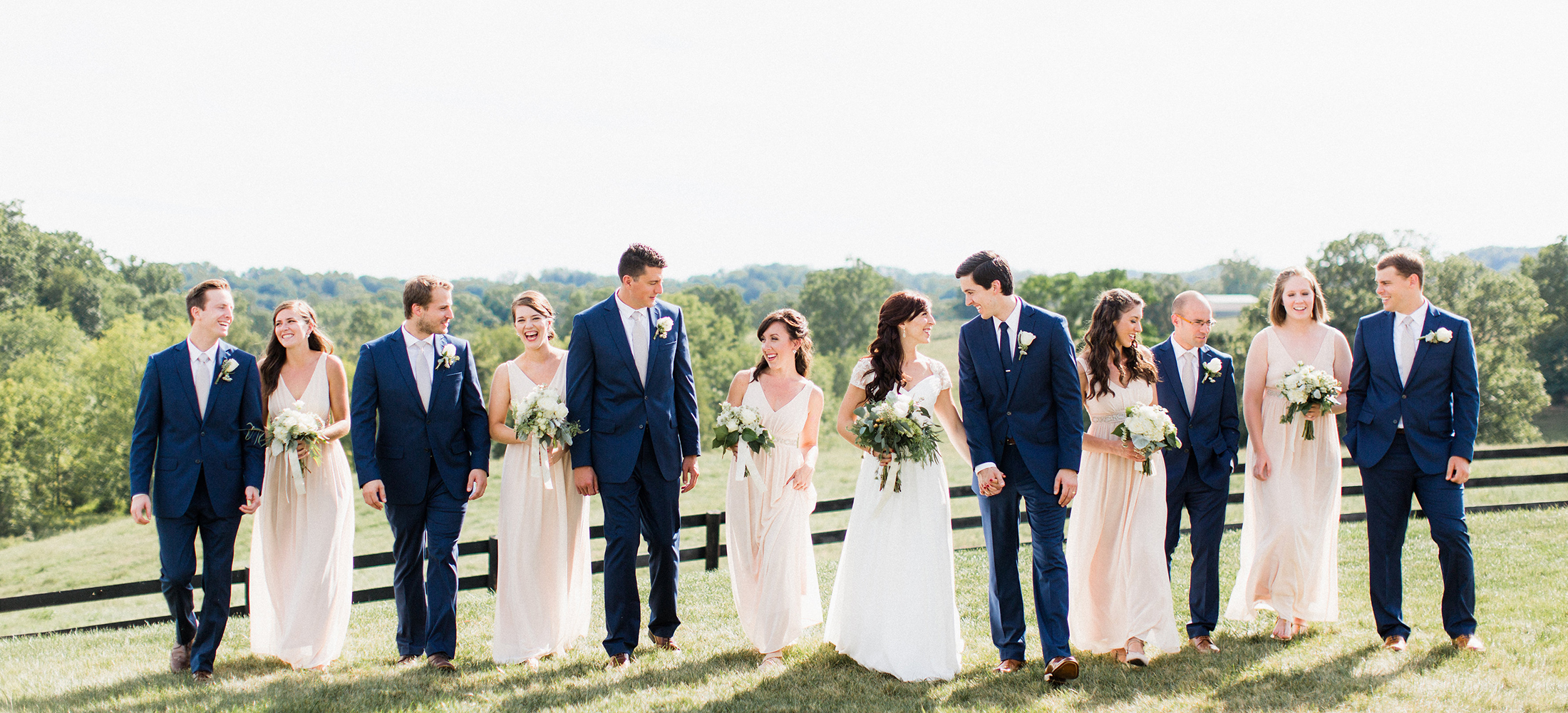 Bridal party walking the hills outside Shadow Creek Weddings wearing navy and blush