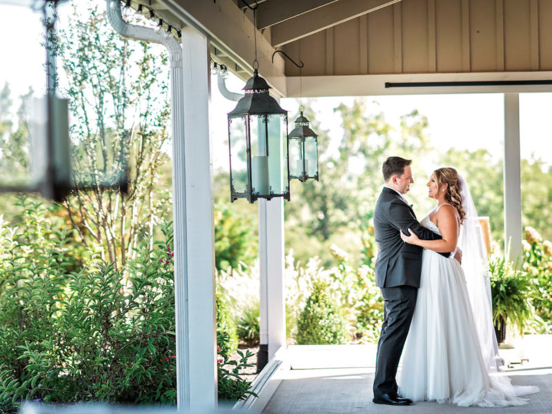 Bride and groom take a picture together on the front porch at Shadow Creek in Loudoun County