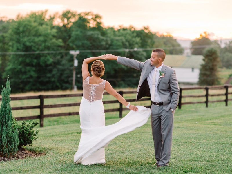Groom twirls his bride on the land at Shadow Creek Weddings and Events in Loudoun County