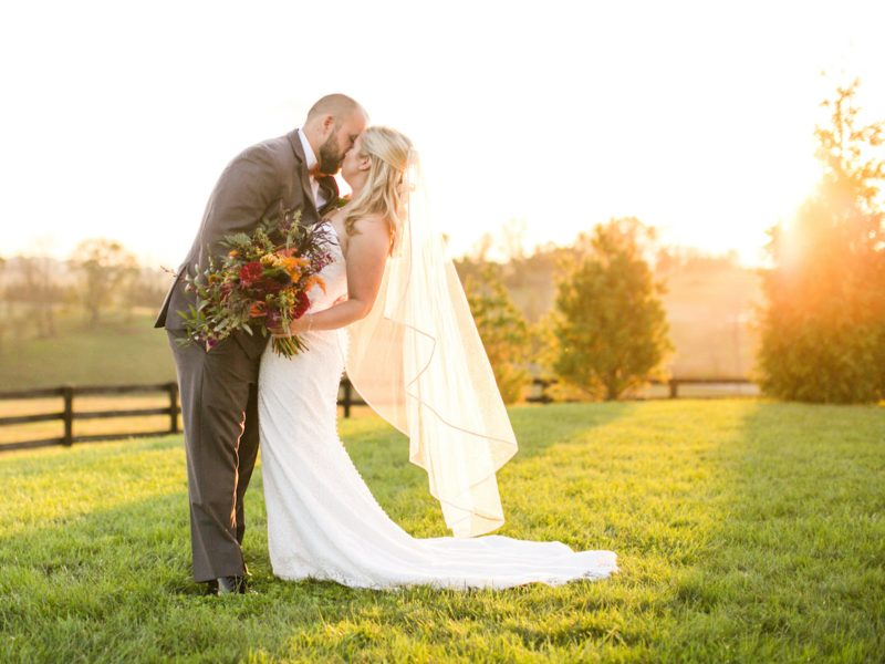 Bride and groom kissing in the sunset with fall bouquet at Shadow Creek
