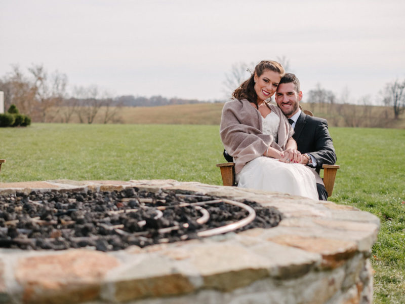 Bride and groom pose by the firepit on their wedding day in Loudoun County