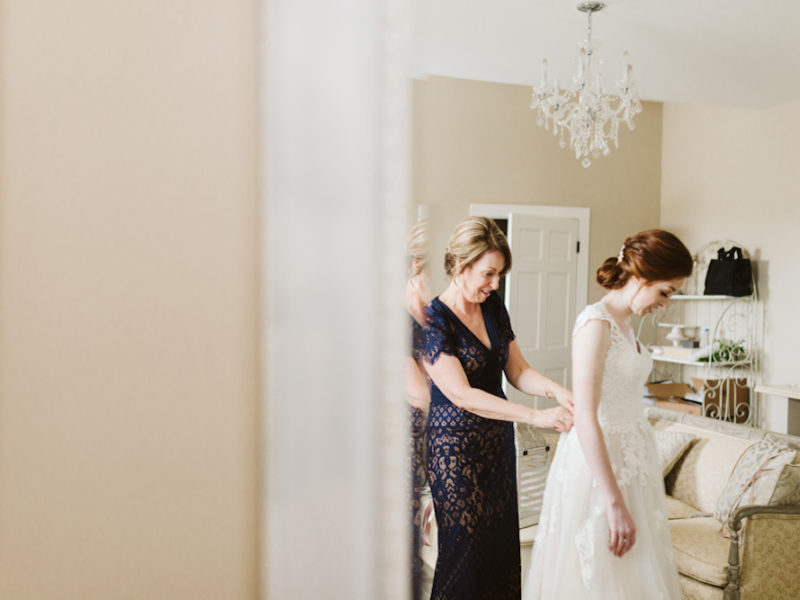 Mother helping daughter on her wedding day