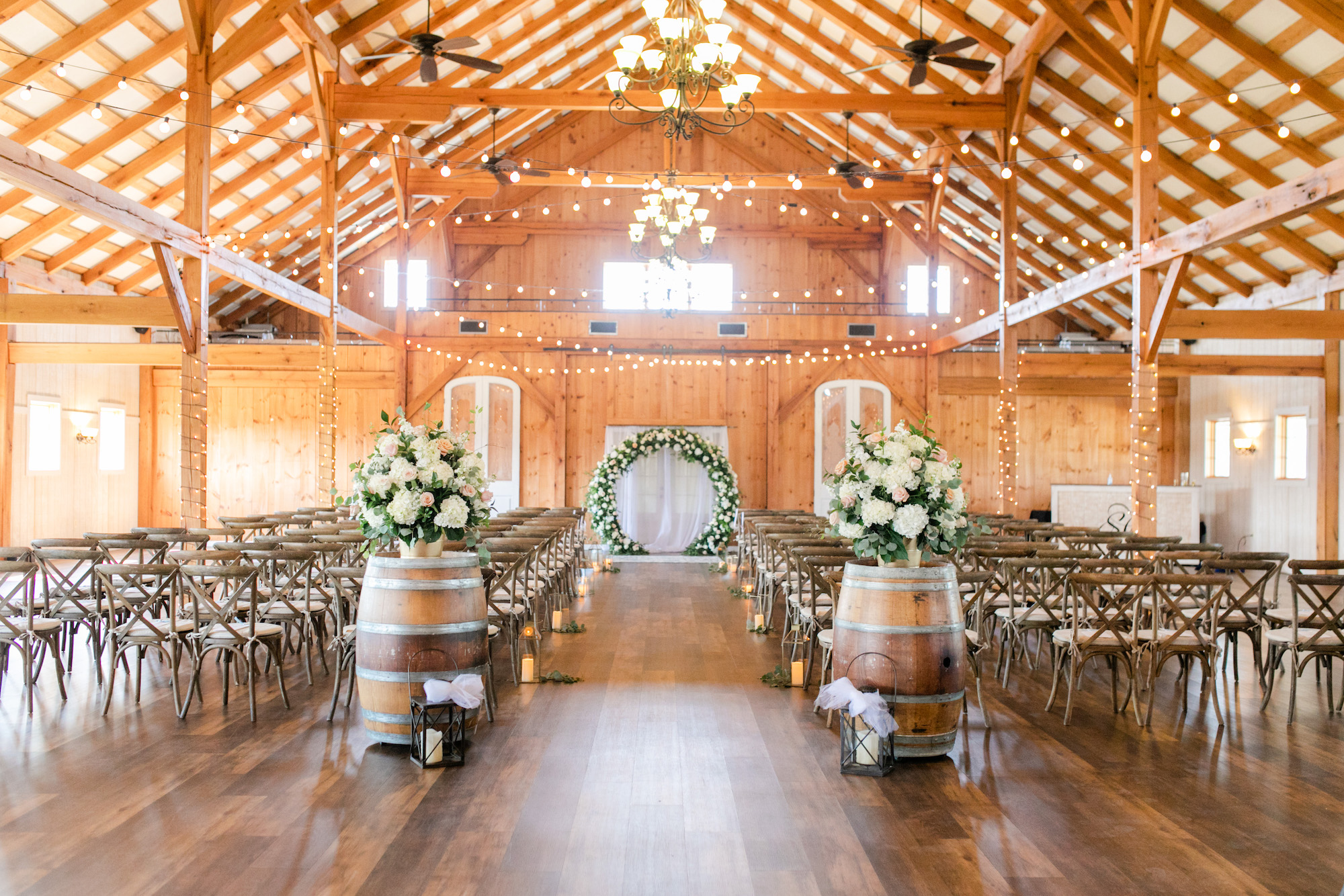 Indoor wedding ceremony design with aisle and floral arch