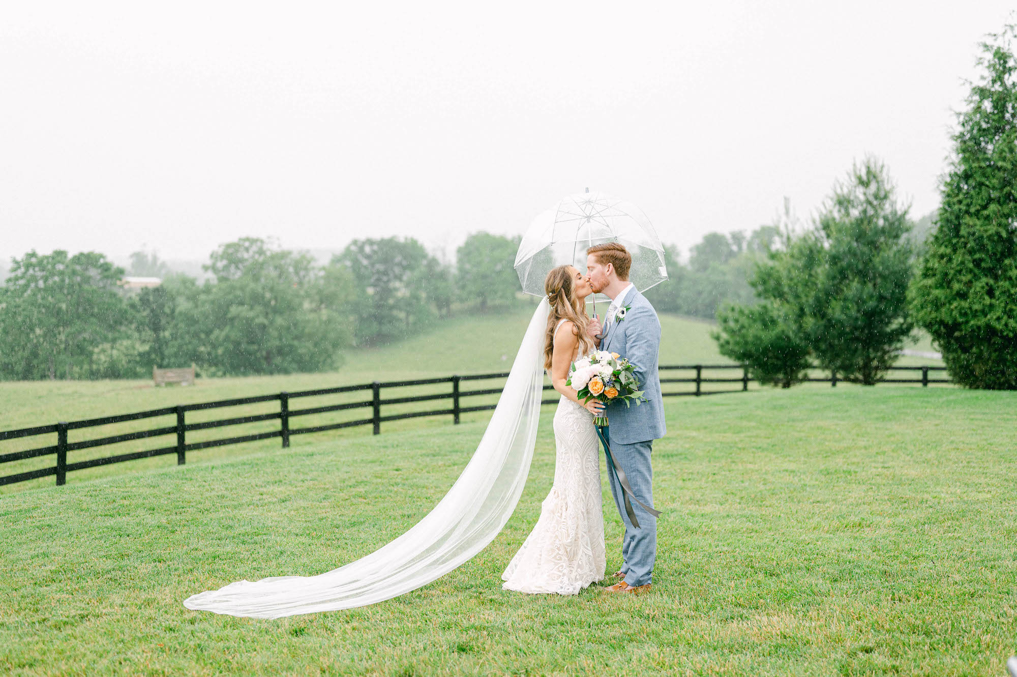 Rainy wedding day with bride and groom at barn wedding venue in green field